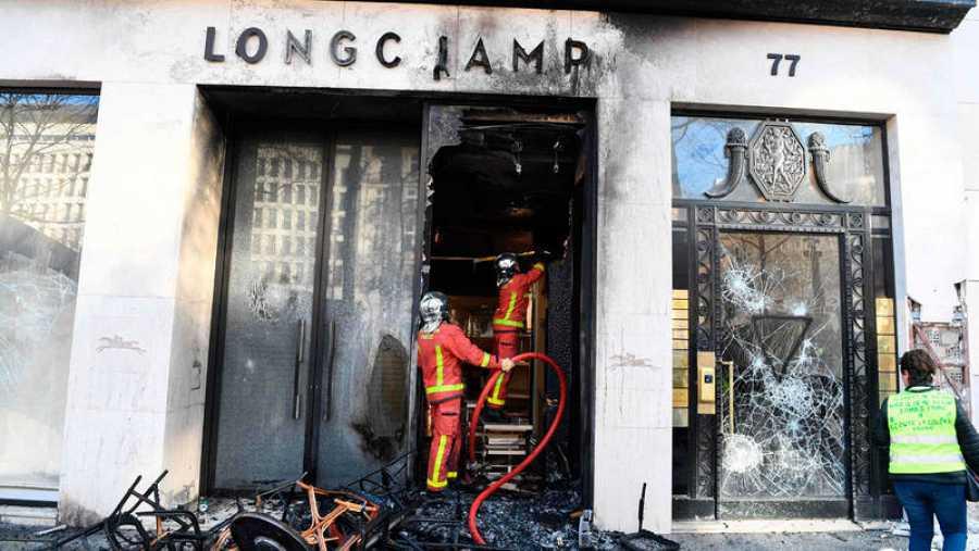 يعمل اثنان من رجال الإطفاء في أحد المتاجر التي دمرت في الاحتجاجات