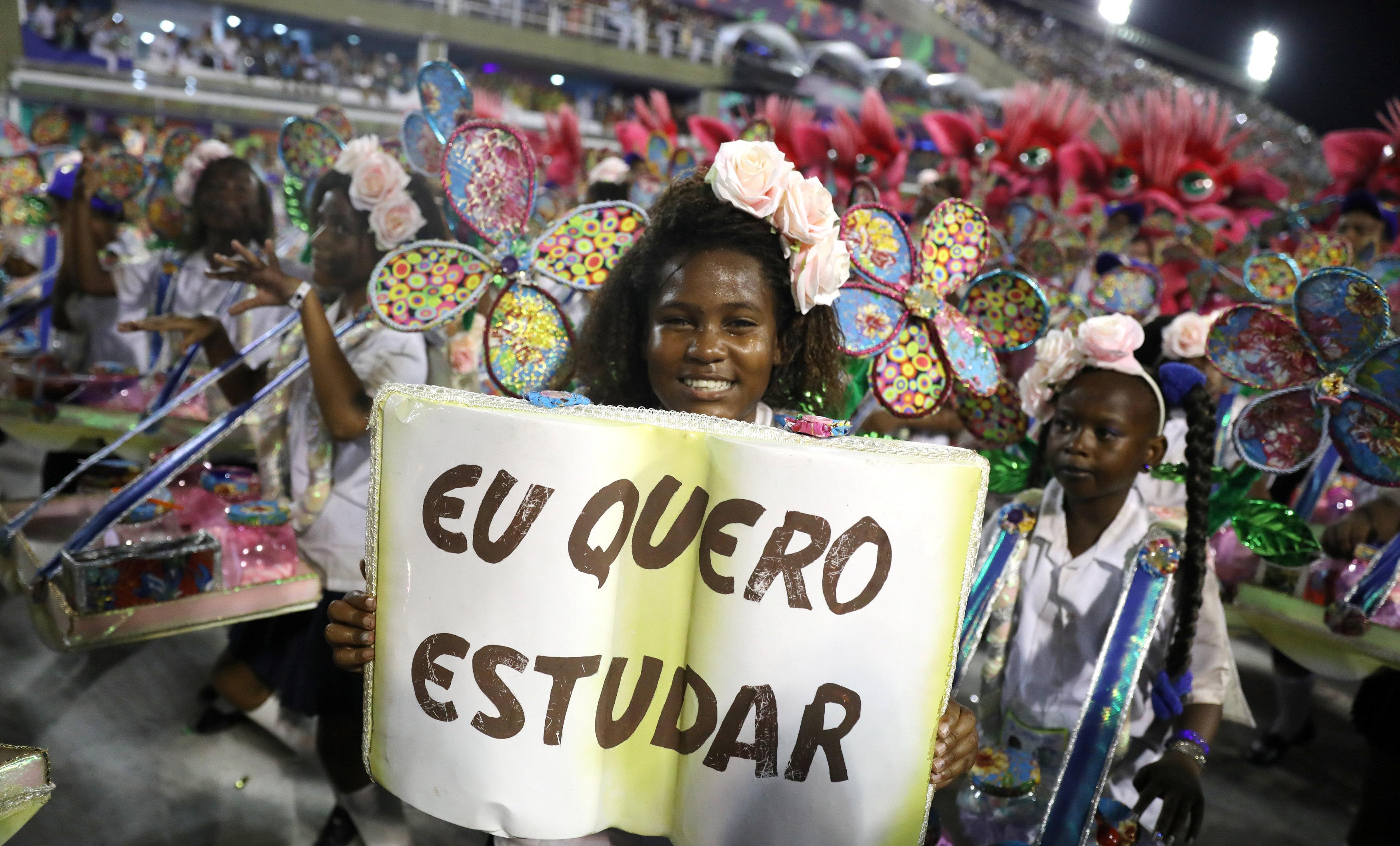 """""""أريد أن أدرس""""، ويقول ملصق هذه الفتاة من مدرسة بيجا فلور السامبا (ريوترز / بيلار أوليفارز)"""
