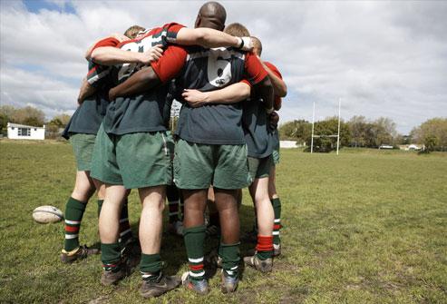 لاعبو لعبة الركبي يقفون في دائرة حول الملعب الرياضي