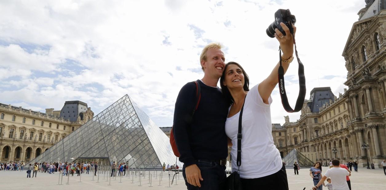 يقف السياح الأستراليون لصورة ذاتية مع هرم متحف اللوفر في الخلفية.  / رويترز / جاكي نايجلن