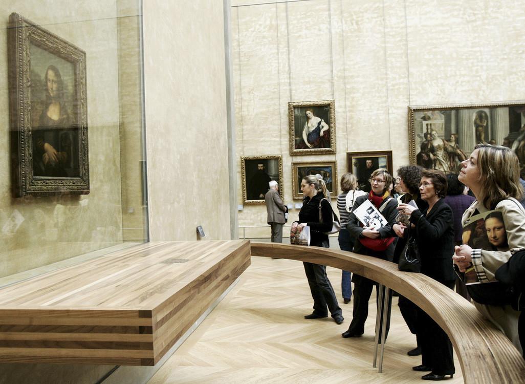 """ينظر الزائرون إلى لوحة """"الموناليزا"""" (لا جيوكندا) التي رسمها ليوناردو دافنشي، خلف زجاج، أكثر أعمال متحف اللوفر.  / ا ف ب / فرانسوا موري"""