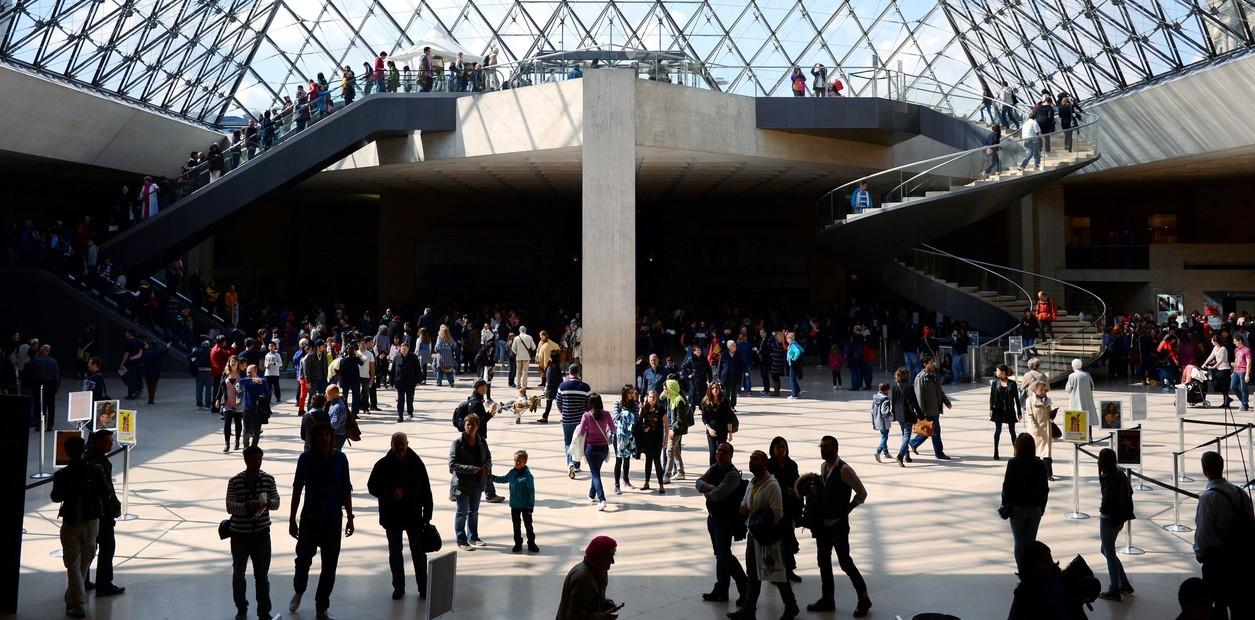 زوار يمشون داخل هرم متحف اللوفر.  / فرانك فايف / اف ب