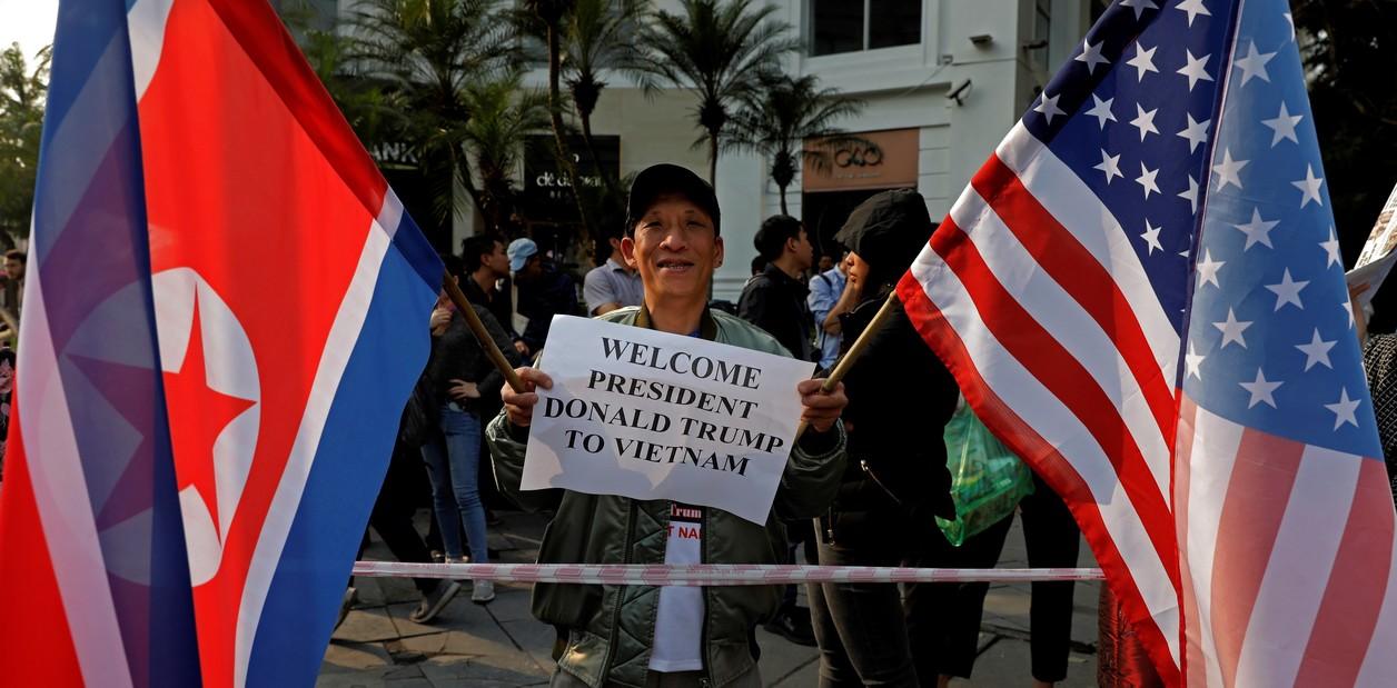 """رجل يحمل لافتة تحمل عنوان """"الترحيب بالرئيس دونالد ترامب في فيتنام"""" بجوار أعلام الولايات المتحدة وكوريا الشمالية خارج فندق ميتروبول، حيث يعقد عشاء الرئيسين.  (صورة اسوشيتد برس / فينسنت يو)"""