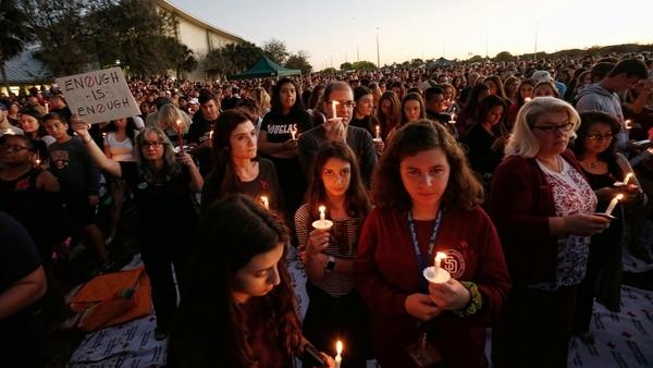 """الآلاف من الناس يحملون الشموع خلال الوقفة الاحتجاجية على ضوء الشموع لضحايا مارجوري ستونيمان دوغلاس المدرسة الثانوية اطلاق النار في باركلاند، فلوريدا.  وقال لافتة (اف ب) """"يكفي ما يكفي"""""""