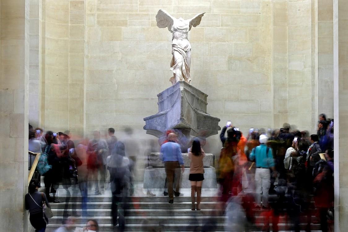 """يراقب الزائرون تمثال """"ساموثرايس"""" المجنح، وهو تمثال من الرخام الهلنستي في متحف اللوفر في باريس.  / رويترز / تشارلز بلاتياو"""