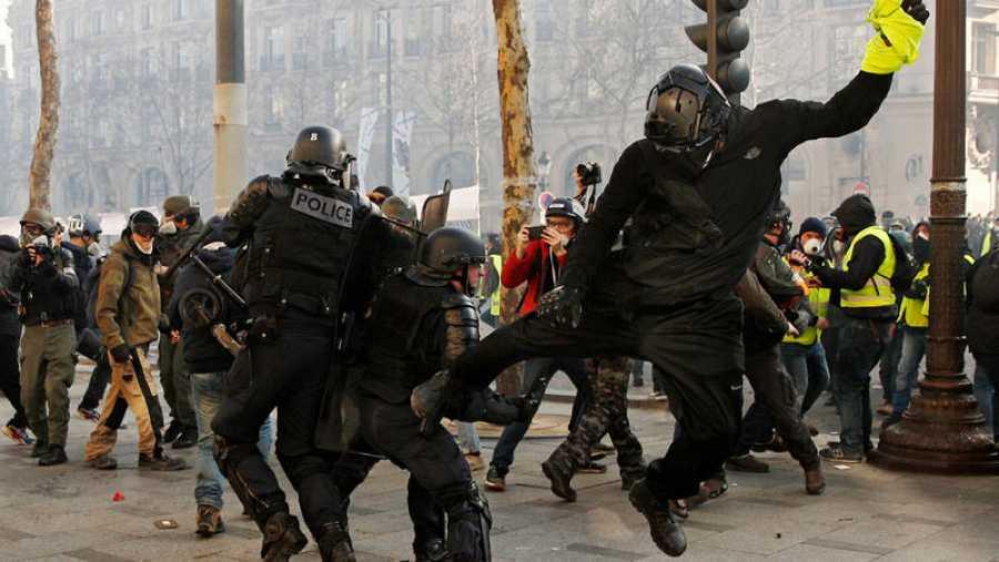 متظاهر يرتدي السترة في يده يهاجم شرطيًا في باريس
