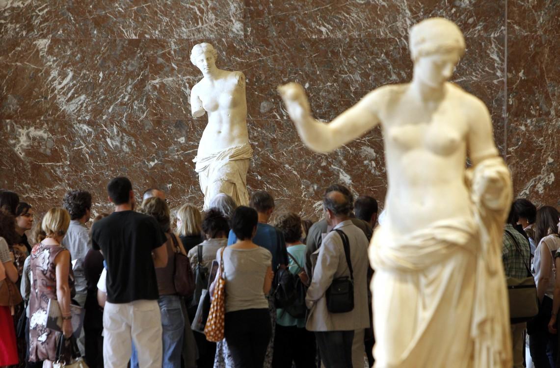 فينوس دي ميلو (الخلفية) في الغرف المخصصة للآثار اليونانية والهيلينية الكلاسيكية في متحف اللوفر.  / AFP PHOTO / PATRICK KOVARIK