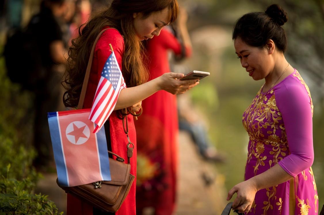 امرأة تحمل أعلاما أمريكية وكورية شمالية بينما تسير على طول بحيرة السيف في هانوي بفيتنام بينما تعقد القمة.  (أ ب / أندرو هارنيك)