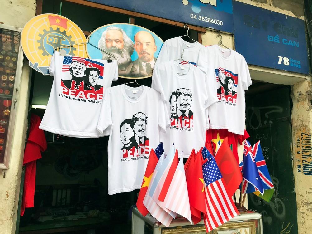 تي شيرت مع وجوه ترامب وكيم، تحت صورة ماركس ولينين، في منطقة محلية في الحي القديم في هانوي.  (EFE / Lucía Leal)