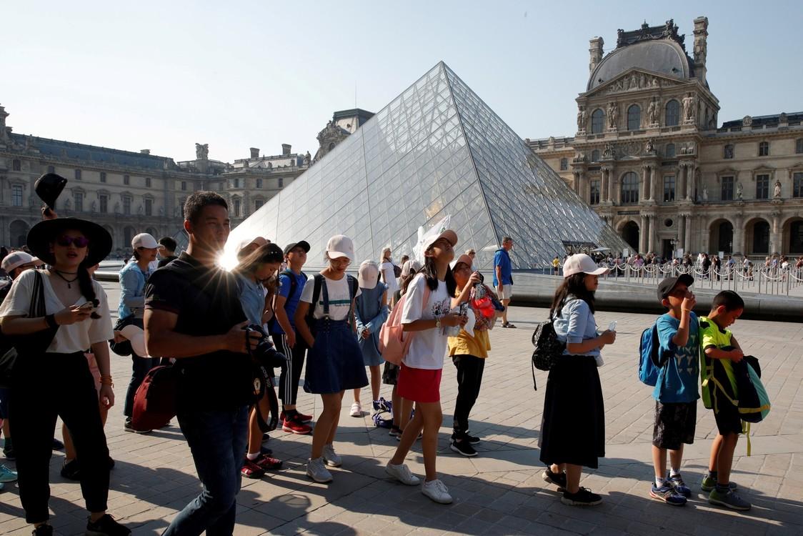السياح أمام هرم متحف اللوفر الذي صممه المهندس المعماري الأمريكي آيوو ولدت في الصين.  / رويترز / فيليب وجوازر