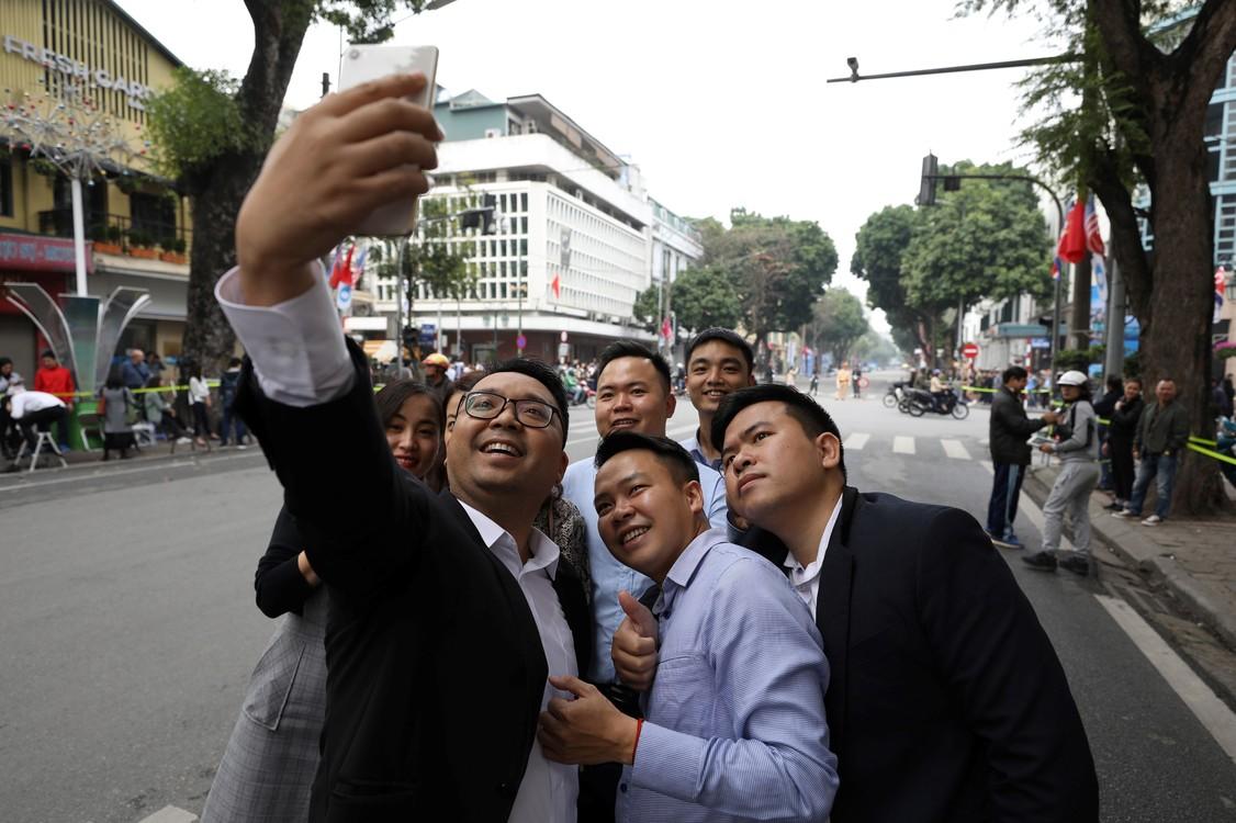 يأخذ الناس صورا ذاتية من أمام فندق في هانوي سوفيتيل متروبول الأسطورة، فيتنام، حيث يلتقي الزعيم الكوري الشمالي كيم جونغ أون ورئيس الولايات المتحدة.  (SeongJoon Cho / Bloomberg)