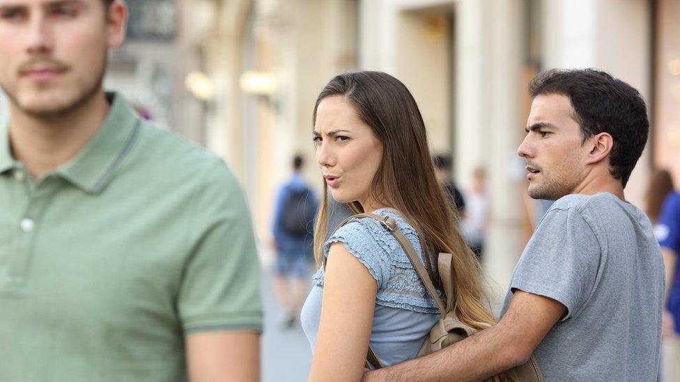 امرأة تشاهد رجلاً آخر أمام شريكه.