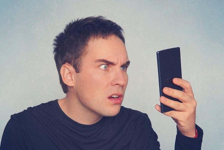 رجل يراقب الهاتف المحمول